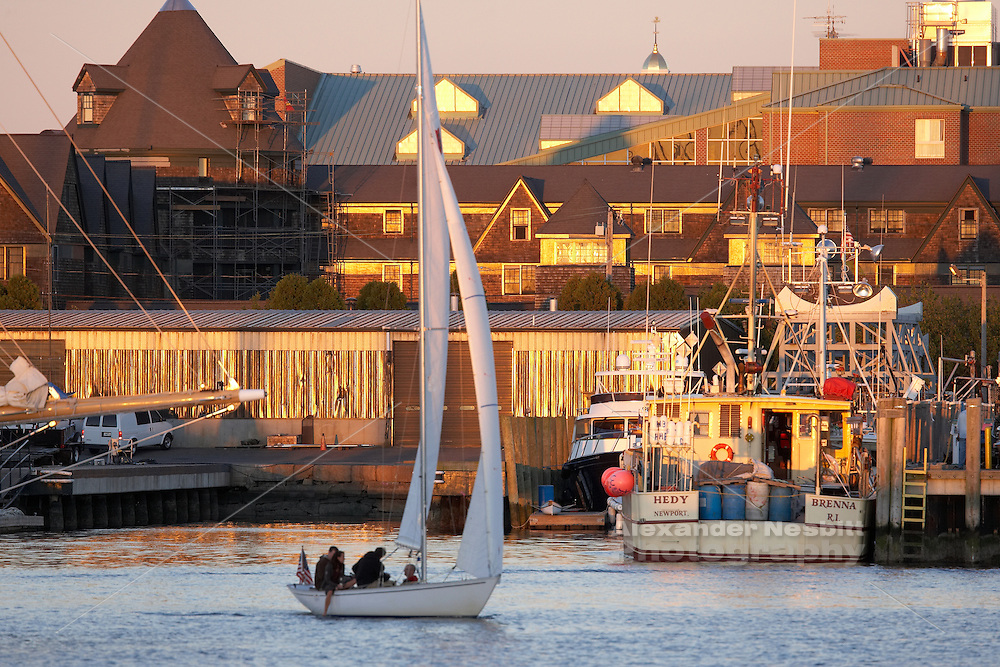 Shields sloop sails slowly through Newport Harbor past the fishing boats at the state pier and brilliant sunset reflections off the Marriot hotel.
