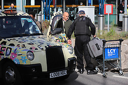 © Licensed to London News Pictures. 10/10/2019. London, UK. A police officer helps a family load luggage into a taxi as Extinction Rebellion protesters block London City Airport. Protesters plan to occupy the terminal building in a 'Hong Kong-style' shutdown as part of ongoing protests calling on government departments to tackle the Climate Emergency. Photo credit: Rob Pinney/LNP
