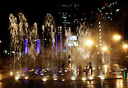 Childrean sitting in circle under water fountain in  Urban Park, Rose Fitzgerald Kennedy Greenway, Boston, MA.Purple neon lights. At night the city's urban landscape is lit and takes on a vibrant dimention.  In these impressions of everyday scenes the artist highlights the bricks, morter and steal that we pass every day but rarely see. The series called Boston Noir is intentionally gritty and edgy like the city at night.