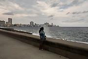 Uma rapariga absorvida nos seus pensamentos junto ao mar, em Havana, Cuba.