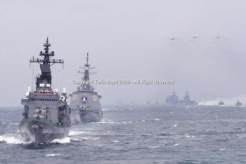This is Japan's AEGIS Destroyer Ashigara (second ship from front) which is used for protection against possible North Korean missile launches. The ship is front is the destroyer Kurama, the flagship of this fleet.<br /> <br /> They are seen here during the Japan Maritime Self-Defense Force Fleet Review 2009 held in the waters off the Miura peninsula on October 25, 2009. This is where Sagami Bay meets the entrance of Tokyo Bay and close to the historical port of Yokosuka where both Japan and the US have a significant naval presence. Taking place every three years, this fleet review features the finest in the Japanese naval fleet which is officially called the Japan Maritime Self Defense Force (JMSDF). This display included about 8,000 sailors, 36 warships and three submarines, as well as numerous support aircraft. The JMSDF is primarily confined to defending Japanese coastal waters which is stipulated in Japan's postwar constitution. But more recently it has played an overseas role by supporting US led coalition forces off Afghanistan and defending ships against piracy off the coast of Somalia. However, Japan is now expected to return to a more pacifist role now that the current administration of Prime Minister Yukio Hatayoma and the Democratic Party of Japan (DPJ) overthrew the conservative Liberal Democratic Party (LDP) from it's is 54 year grip of power in August 2009. The Japanese navy which is viewed as the strongest in Asia is seen as an important regional balance due to China's increasing naval power, as well as regularly monitoring North Korean activity from the Sea of Japan. On hand to witness this event were several high ranking Japanese politicians including PM Hatoyama who was a flown in helicopter, as well as an international cast of VIP that included military heads and embassy officials from around the world.