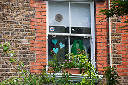London, UK. 14 June, 2019. Grenfell tributes in the window of a house on the route of a second anniversary silent walk by family members from St Helen's Church to the foot of Grenfell Tower to lay flowers in memory of loved ones who perished in the  Grenfell Tower fire on 14th June 2017.