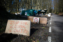 © Licensed to London News Pictures. 02/03/2017. Coldharbour, UK. A sign invites drivers to 'STOP FOR A CUPPA AND A CHAT at the 'Protection Camp' on Leith Hill. Activists have constructed and occupied a fort and some trees on the site of a proposed oil well. Planning permission for 18 weeks of exploratory drilling was granted to Europa Oil and Gas in August 2015 after a four-year planning battle. The camp was set up by protestors in October 2016 in order to draw  attention to plans to drill in this Area of Outstanding Natural Beauty (AONB) in the Surrey Hills. The camp has received support from the local community.  Photo credit: Peter Macdiarmid/LNP