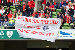DUBLIN, REPUBLIC OF IRELAND - Wednesday, May 14, 2014: Stewards try to confiscate a Liverpool supporters' banner 'We told you they lied. Don't by the Sun. Justice for the 96' during a postseason friendly match against Shamrock Rovers at Lansdowne Road. (Pic by David Rawcliffe/Propaganda)