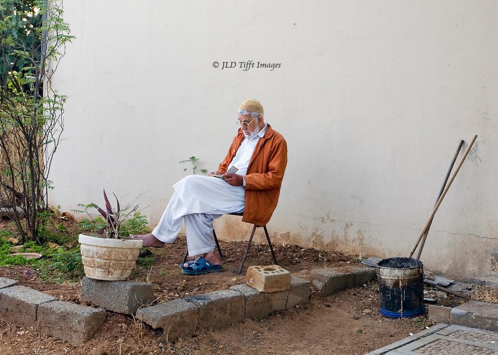 Job's tomb, near Salalah, Oman.  Seated man reading outside..