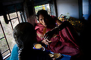 Thiruvani Bhai aged 80 (right) picks a fallen bird feather from her friend's sari as they chat over lunch on the train 9th July 2009. She is travelling 2810km from Gwalior to Kanyakumari with her husband to visit the Rameshwaram Temple.. .6318 / Himsagar Express, India's longest single train journey, spanning 3720 kms, going from the mountains (Hima) to the seas (Sagar), from Jammu and Kashmir state of the Indian Himalayas to Kanyakumari, which is the southern most tip of India...Photo by Suzanne Lee / for The National