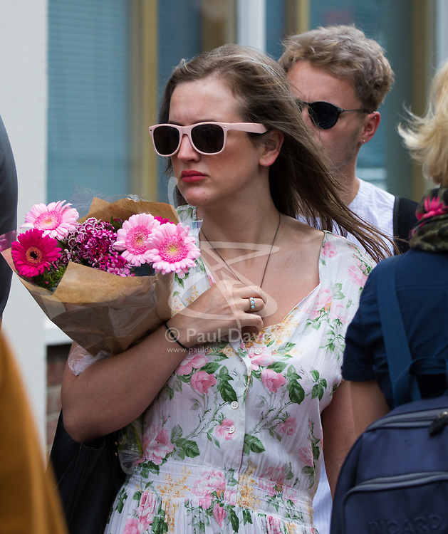 London, June 4th 2017. A woman arrives at Borough High street with a bouquet of flowers during a massive policing operation in the aftermath of the terror attack on London Bridge and Borough Market on the night of June 3rd which left seven people dead and dozens injured