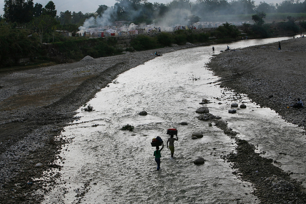 Women balance bags on their heads as they wade through a river to a makeshift camp for earthquake survivors in Leogane, Haiti, Thursday, Feb. 11, 2010. (AP Photo/Rodrigo Abd)