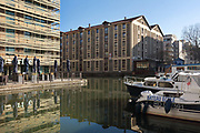 Holiday Inn Express (left) on the Canal de la Villette, and boats (right) moored in the harbour of the Bassin de la Villette or La Villette Basin, in the 19th arrondissement of Paris, France. The basin is a large artificial lake linking the Canal de l'Ourcq to the Canal Saint-Martin, dug in the early 19th century and filled in 1808 to provide the city of Paris with fresh drinking water. Picture by Manuel Cohen