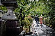 A wedding couple walks through a garden in Higashiyama, for some photos.