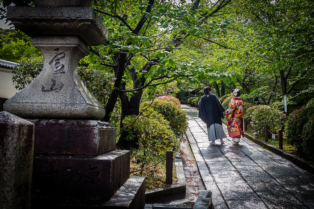 A wedding couple walks through a garden in Higashiyama, for some photos.