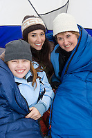 Family sitting in tent, smiling, portrait