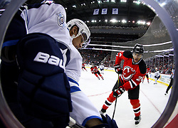 Jan 17; Newark, NJ, USA; New Jersey Devils defenseman Bryce Salvador (24) and Winnipeg Jets left wing Evander Kane (9) battle for the loose puck during the first period at the Prudential Center.