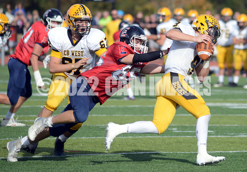 Central Bucks West quarterback Joshua Crecca (9) eludes a tackle by Central Bucks East's J.W. Scollins (5) in the third quarter Saturday, October 21, 2017 at Central Bucks East in Buckingham, Pennsylvania. (WILLIAM THOMAS CAIN / For The Philadelphia Inquirer)
