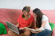 Two teens studing on a couch