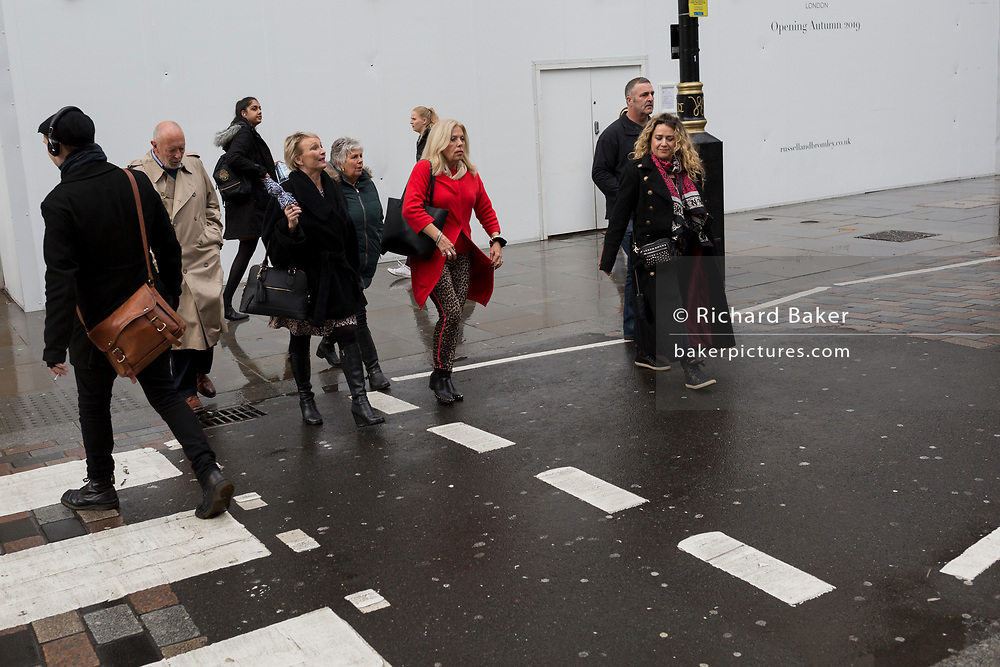 After heavy rainfall, Londoners and visitors walk along Long Acre, Covent Garden, on 24th October 2019, in Westminster, London, England.