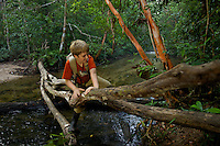 A 9 year-old boy crosses a rain forest river using a natural fallen tree bridge.