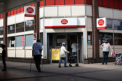 © Licensed to London News Pictures .  07/05/2020 . Salford, UK. People stand two metres apart from one another as they queue outside a post office at Salford Shopping City . Photo credit : Joel Goodman/LNP