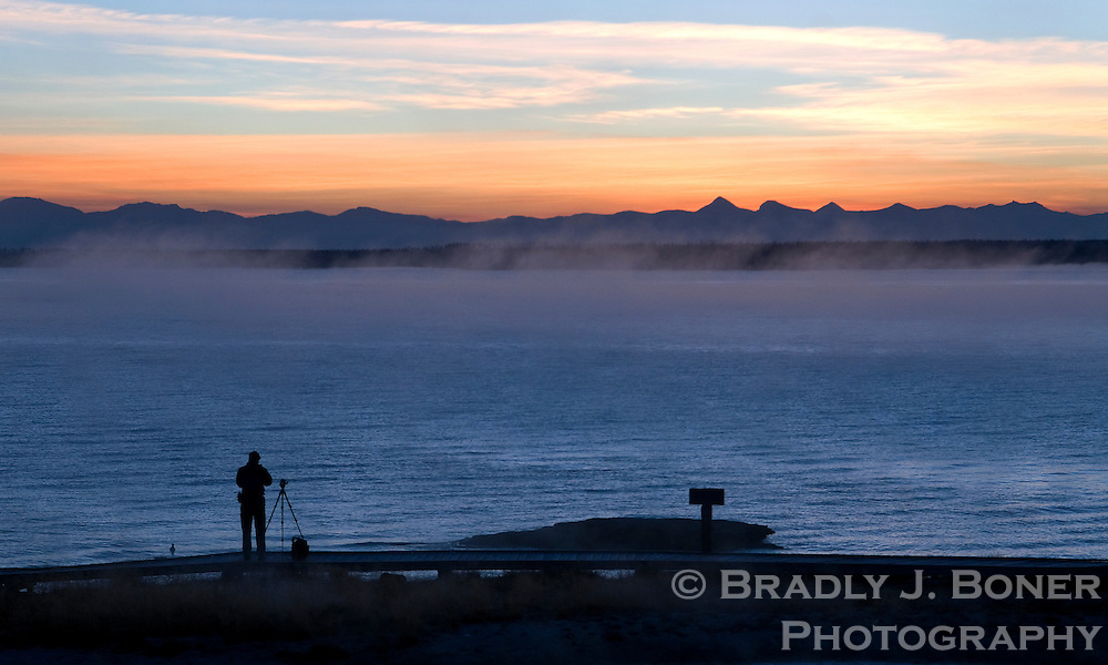 A photographer takes in the view of Jackson Lake from the West Thumb Geyser Basin at sunrise in Yellowstone National Park.