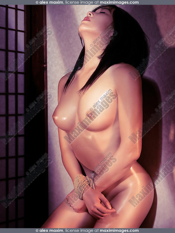 Beautiful naked Japanese woman with her hands tied with rope leaning against a wall