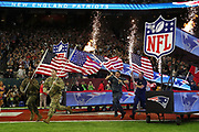 Members of the U.S. military run onto the field carrying American flags as fireworks go off in the background before the New England Patriots Super Bowl LI football game against the Atlanta Falcons on Sunday, Feb. 5, 2017 in Houston. The Patriots won the game 34-28 in overtime. (©Paul Anthony Spinelli)