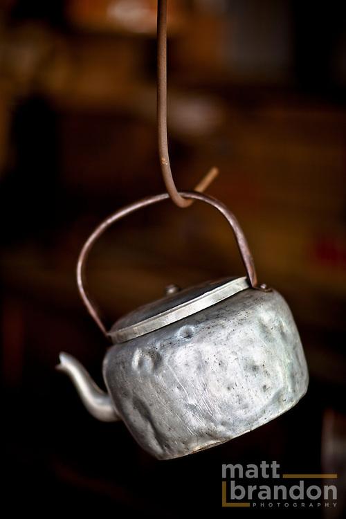 An old aluminum teakettle hangs on a steel hook in easy reach.