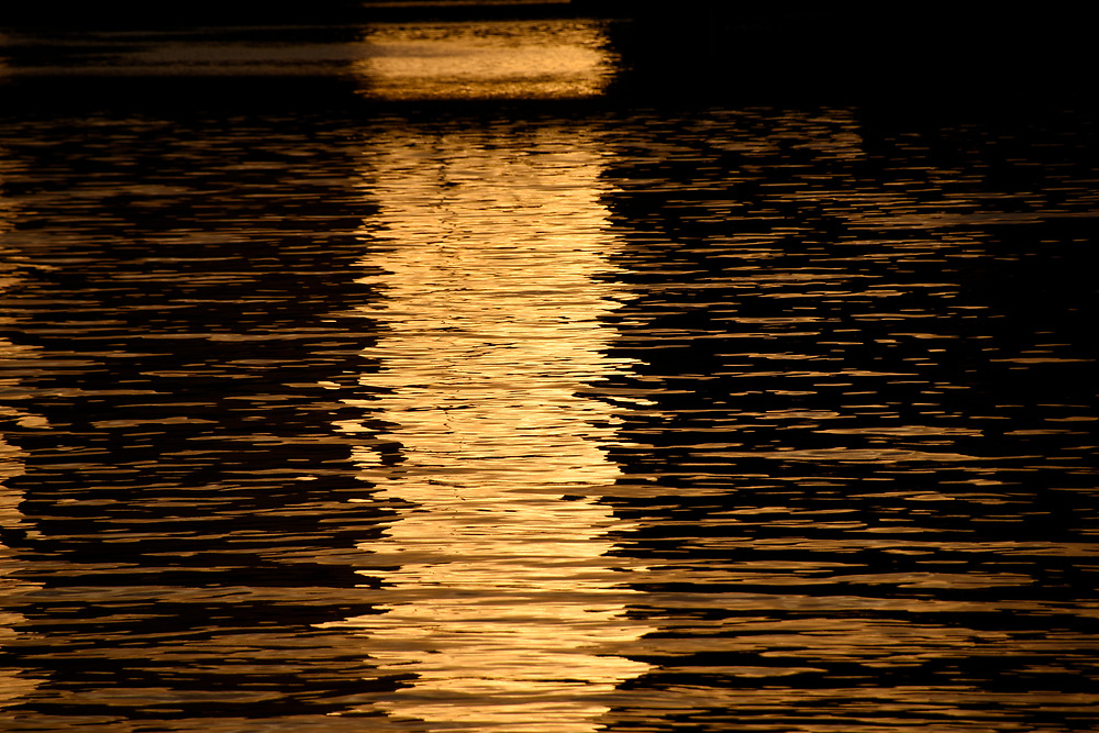 Reflections of a gold sunset abstract on the river yarrow