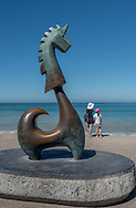 On the Puerto Vallarta malecon a Mother and daughter stand looking at the blue Bay of Banderas from behind The Good Fortune Unicorn sculpture by Aníbal Riebeling.