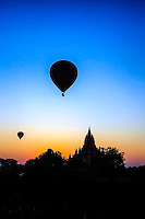 Balloon Sunrise: Hot air balloons start their ascent over the silhouetted ancient ruins in the early morning sky, Bagan Myanmar.
