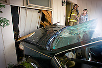 JEROME A. POLLOS/Press ..Lt. Larry Sande, with Kootenai County Fire & Rescue, and Audrey Roseth inspect the damage to her home after a car crashed into it Thursday in Fernan. No one was injured in the crash that was caused by a driver who lost consciousness due an illness.