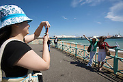 Brighton Pier. Tourists taking souvenir photographs.