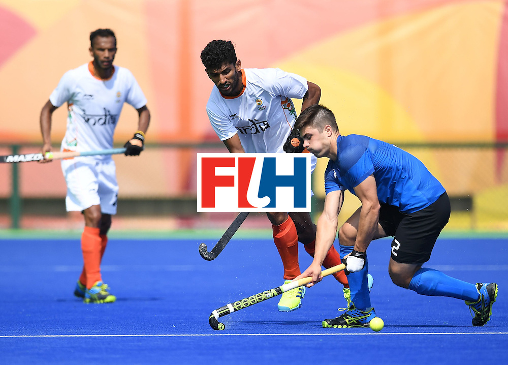 India's Uthappa Sannuvanda (C) fights for the ball with Argentina's Gonzalo Peillat  during the men's field hockey Argentina vs India match of the Rio 2016 Olympics Games at the Olympic Hockey Centre in Rio de Janeiro on August, 9 2016. / AFP / MANAN VATSYAYANA        (Photo credit should read MANAN VATSYAYANA/AFP/Getty Images)