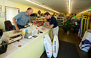 Lynn Burrell (from left) of Marion talks with Dan Lord of Cedar Rapids as he purchases some sunflower seeds and cracked corn at Frontier Garden Center, 1941 Blairs Ferry Road NE, in Cedar Rapids, on Thursday, September 8, 2011.