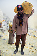 A sulfurmineworker posing with a heavy load of sulfur on his shoulder. Ijen mine, Banyuwangi