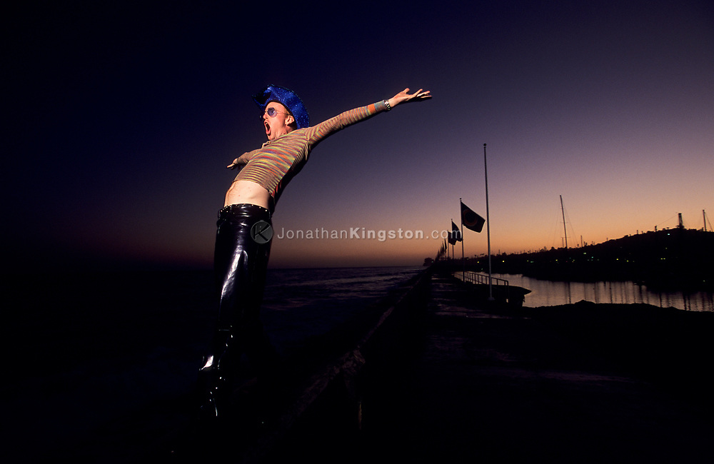Low angle view of a young man wearing a blue cowboy hat standing on a wall near the ocean with outstretched arms and yelling in Santa Barbara, California. (releasecode: jk_mr1030) (Model Released)