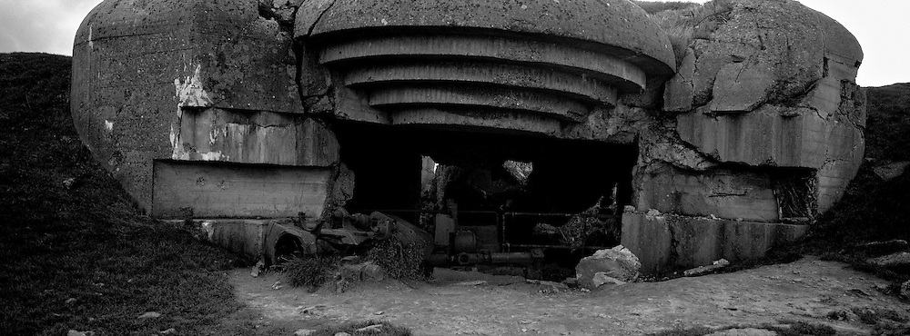 LONGUES-SUR-MER, FRANCE - NOVEMBER 21: The shattered remains of a 155m canon lies at the entrance to a German bunker, 21 November, 2008, in Longues-sur-Mer, France. The well-camouflaged four-gun battery was foiled by a irate French farmer and his blind son after occupying Germans prevented him from grazing his livestock and growing crops near the bunkers. The farmer paced the distance between the bunkers, observation posts and trenches, then passed the information to his blind son who was able to move between villages without raising suspicions and passed the information to the French Resistance. The Resistance then transmitted the information to the English who, on D-Day, had the exact co-ordinates of the fortification. D-Day is regarded amongst historians as possibly the most defining day of the 20th Century, when allied forces comprising of 175,000 fighting men transported by 5,333 ships and 11,000 aircraft, landed in Nazi-occupied France and went on to liberate Europe. (Photo by Warrick Page)