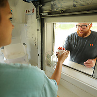 Dawson Crawford, an employee at Rockin' Robin Shaved Ice & Refreshments, hands a Cherry snow cone to customer Brent Taylor, of Myrtle, on a warm Labor Day in at Ballard Park in Tupelo.