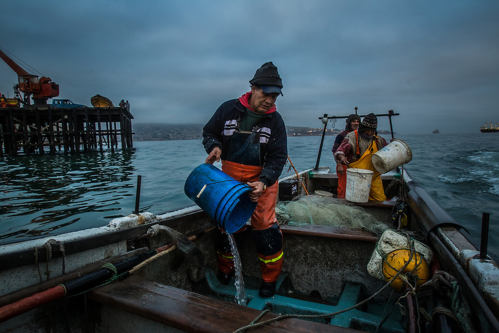 VALPARAISO, CHILE - MARCH 18, 2014: Artisanal fishermen   clean the deck of their boat with buckets after fishing for hake fish off the coast of Valparaiso, Chile. Hake stocks have suffered in Chile, and the government is working to regulate the fishing industry in effort to make it more sustainable. PHOTO: Meridith Kohut for The World Wildlife Fund