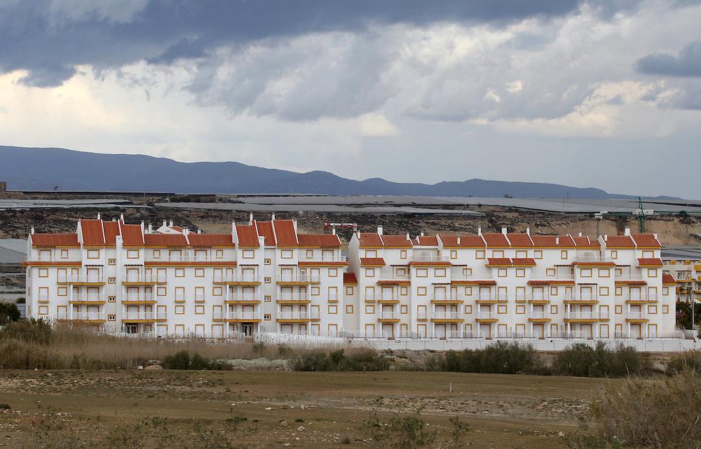 """EUROPE - SPAIN - EL EJIDO ; Illegal Immigration - VEGETABLE & FRUIT Production in Andalusia ; EL PLASTICO ; Exploitation of African workers;.The fruits and vegetables grown in the area are worth about $1.8 billion a year. Most of the workers are Moroccans, often called """"Moros"""" in reference to the Moors who ruled southern Spain for 700 years; Europa - SPANIEN - Landwirtschaft.Die Region um El Ejido, Provinz Almeria in Andalusien, gilt als Europas  größter agrarindustriell genutzter """"Wintergarten"""". Unter ca. 36.000 Hektar Plastik (Treibhäusern) wird ganzjährig Obst und Gemüse angebaut, welches zum Großteil in Supermärkten in Nordeuropa, Deutschland und England verkauft wird... Unter den Plastikplanen werden ca. 60.000, meist illegale Einwanderer aus Marokko, Schwarzafrika, Osteuropa beschäftigt. Arbeitsschutz und Mindestlöhne werden nicht eingehalten. .HIER: Neubaugebiet südlich vom El Ejido, Bauboom.21.03.2007.Copyright: Christian Jungeblodt"""