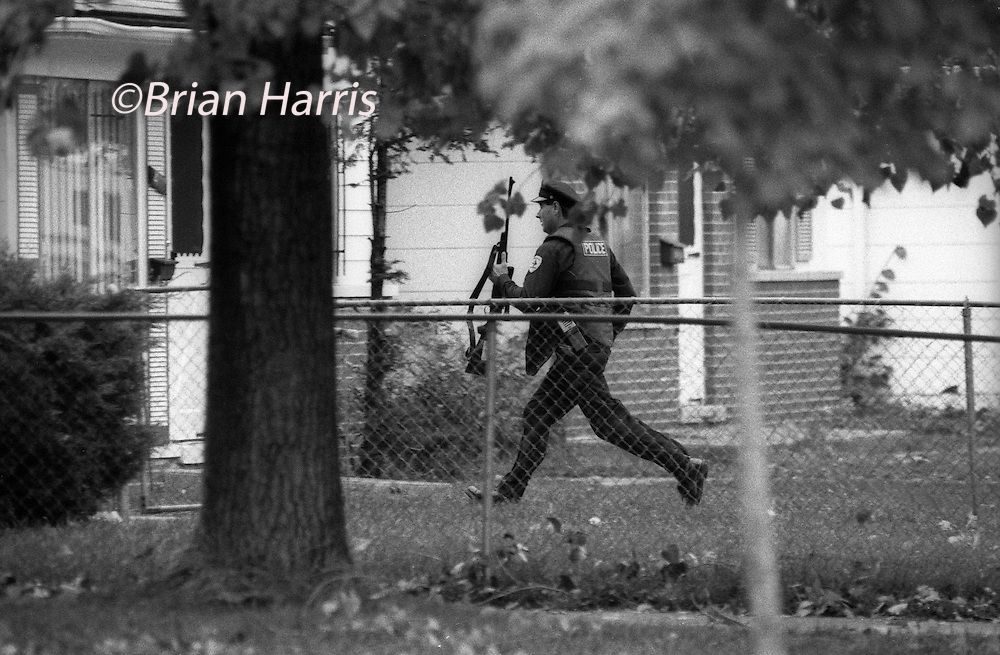 Detroit USA. 1988. Police slaying during siege on the north side of Detroit. 1988<br /> Two Police officers, Lieutenant James Schmit and Police Officer Frank Walls died during a house siege in North Detroit, October 1988<br /> Policemen reacting to gunshots from the building.<br /> Copyright owned photograph the Independent Newspaper&copy; 1988