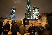 """Gastarbeiter, meist aus Tadjikistan, vor ihren ärmllichen Unterkünften im Schatten ihrer Bausstelle, dem Business Center """"Moscow-City"""" im Hintergrund. Tadjik guest workers in front of their poor huts in the shadow of the Skyscrapers on which they are working on: the business centre """"Moscow City"""" (Background)"""