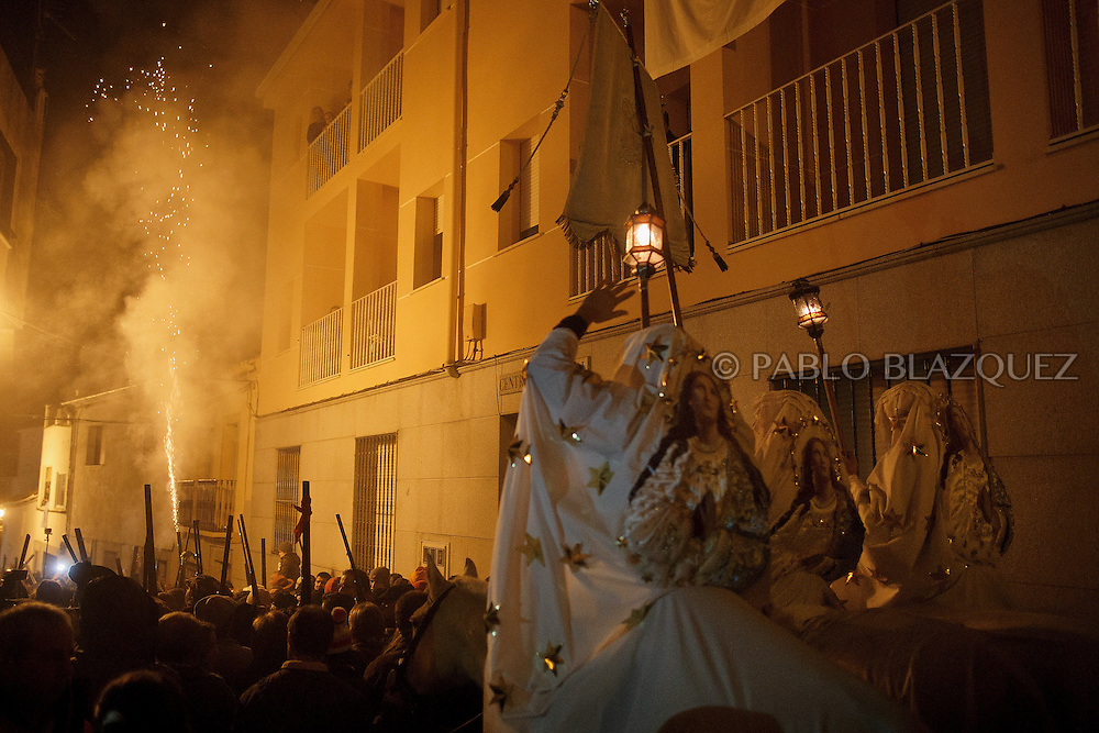 "Horsemen carry a banner with the image of Immaculate Conception as revelers shoot blanks with their shotguns during the ""La Encamisa"" Festival on December 7,  2014 in Torrejoncillo, Extremadura region, Spain. ""La Encamisa"" is an ancient festival in honor of Immaculate Conception. Hundreds of horsemen wearing a white sheet gather outside the church in the main square. The procession starts when a banner with the image of Immaculate Conception is delivered to the horse rider steward and people cheer and shoot blanks. There are bonfires along the way where people gather to chat, eat traditional sweets and drink local wine. The origin of this tradition is unknown but it is believed the festival comes from a military event in which people from Torrejoncillo were involved. The war in Flanders in 1585, the Battle of Pavia or a legend of the siege suffered by city of Coria. (© Pablo Blazquez)"