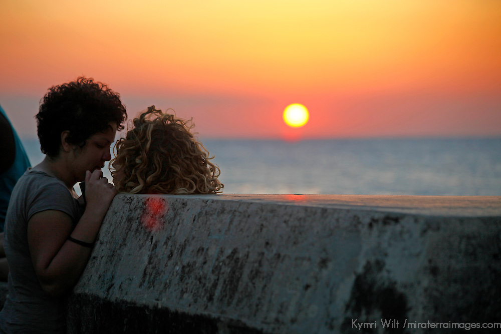 Central America, Cuba, Havana. Couple share a sunset moment on the Malecon in Havana.