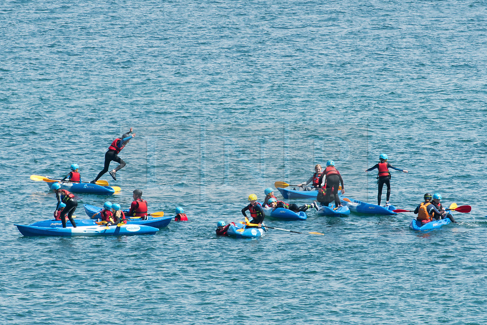© Licensed to London News Pictures. 22/05/2019. Dorset, UK. Young people taking part in water activities jump in the sea from their canoe in Swanage Bay on a hot sunny day in Dorset, UK. Photo credit: LNP