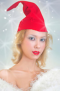 Christmas colours concept young model with red cap and white fur coat on white background