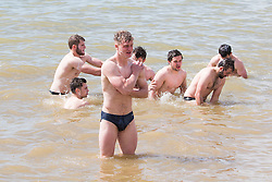 """© Licensed to London News Pictures. 01/05/2016. Brighton, UK. The Dursley Rugby Club spend some time on the beach in Brighton during their Brighton Tour 2016. New tour members are being """" initiated"""" with a morning swim. Photo credit: Hugo Michiels/LNP"""