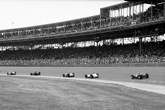 Jack Brabham (right) in his novel little Cooper mammal trails a pack of Roadster dinosaurs at Indy 1961