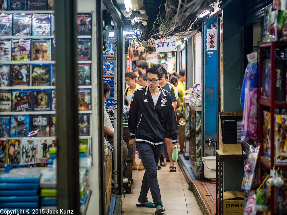 11 OCTOBER 2015 - BANGKOK, THAILAND: A man walks through Saphan Lek market on what Bangkok city government is saying is the last day of business for the market. Many shops in the market are already closed. Street vendors and illegal market vendors in the Saphan Lek area will be removed in the next two weeks as a part of an urban renewal project coordinated by the Bangkok Metropolitan Administration. About 500 vendors along Damrongsathit Bridge, popularly known as Saphan Lek, have until Monday, October 11,  to relocate. Vendors who don't move will be evicted. Saphan Lek is one of several markets and street vending areas being closed in Bangkok this year. The market is known for toy and replica guns, bootleg and pirated DVDs and CDs and electronic toys.    PHOTO BY JACK KURTZ