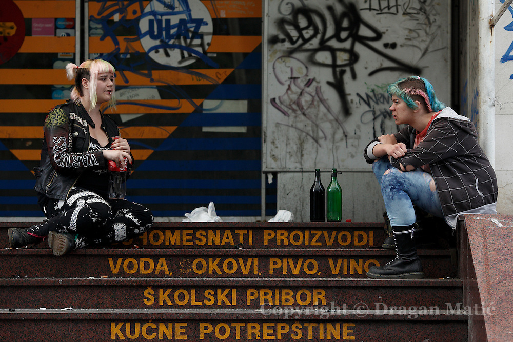 Punk girls drink in front of ruined shop near the main railway station.