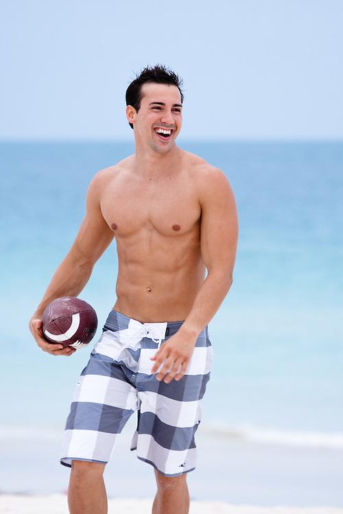 Man playing football on beach